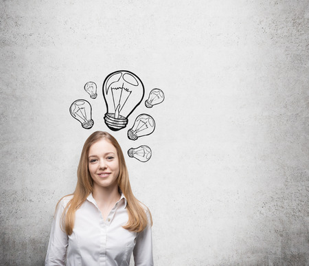 ingenuity: Smiling young beautiful business lady is thinking about new innovative ideas. Light bulbs are drawn on the concrete wall behind the lady. Stock Photo