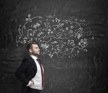 business development: Confident handsome businessman is looking through the problems of business development process. Business icons are drawn on the dark wall.