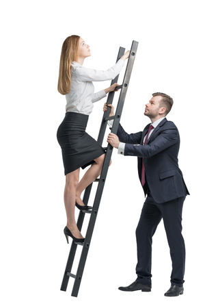 corporate ladder: Young handsome businessman is holding a ladder for the lady in a formal clothes to boost her ideas. The concept of the success and team working