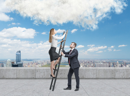 scaling ladder: Young handsome businessman is holding a ladder for the lady in a formal clothes to boost her ideas. The concept of the success and team working. On the roof terrace in the Manhattan, New York.