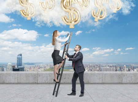 striving: Businessman holds a ladder for the business lady. The concept of the teamwork. On the roof terrace in Manhattan. Dollar icons falling from the sky. Stock Photo