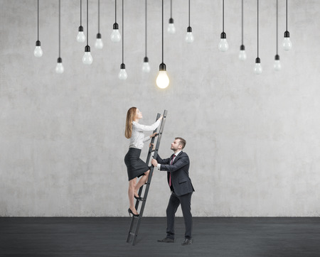 scaling ladder: Businessman holds a ladder for the business lady. The concept of the teamwork and cooperation.