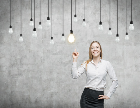 hanging on: Business woman is pointing out the light bulbs. The concept of the innovative business strategy. Concrete background. Stock Photo