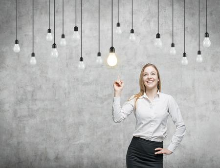 bombilla: Mujer de negocios está señalando las bombillas. El concepto de la estrategia de negocio innovadora. Fondo concreto.