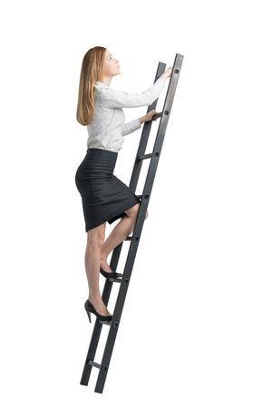 Schöne blonde junge Frau klettert auf die Leiter. Isoliert auf weißem Hintergrund.