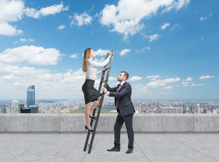 scaling ladder: Businessman is holding a ladder for the business lady. The concept of the teamwork. On the roof terrace in the Manhattan, New York. Falling dollars from the sky. Stock Photo