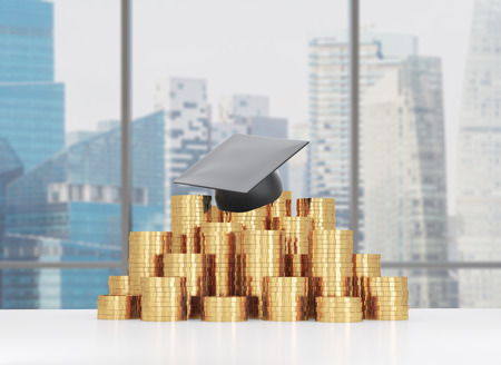 lecture theatre: Graduation hat is laying on the coins pyramid. A concept of a high price for the university education. Panoramic lecture theatre background. Stock Photo