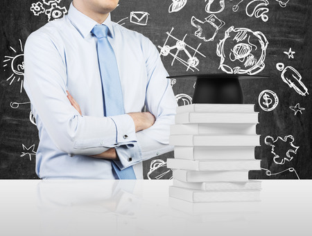 tertiary: Student with the crossed hands is standing in front of the books and a graduation hat. Educational icon on the background. Stock Photo