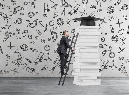graduation suit: A student is climbing up to get university degree. Pile of books and a graduation hat as a prize.Concrete background with educational icons.