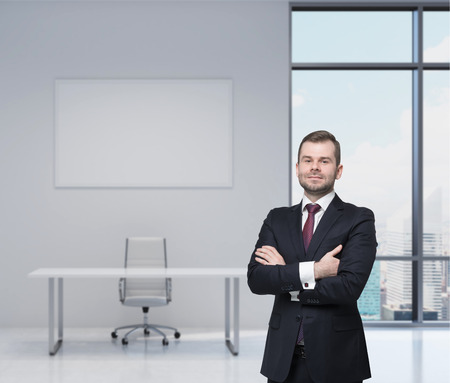 undertaker: Smiling handsome businessman in a black suit with the crossed arms. Modern workplace in an office. New York view. Stock Photo
