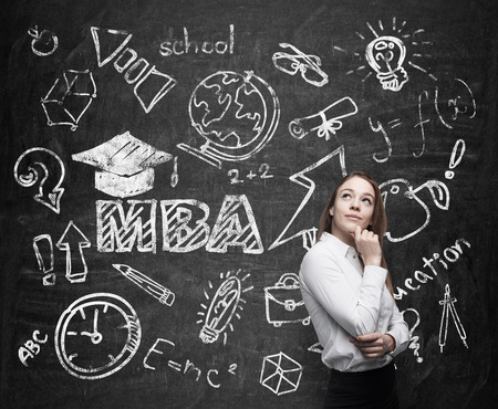 master degree: A lady is pondering over the business degree. A concept of the MBA degree. Drawn educational icons on the chalkboard.