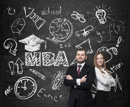 business degree: Young students are pondering over the business degree. A concept of the MBA degree. Drawn educational icons on the chalkboard.