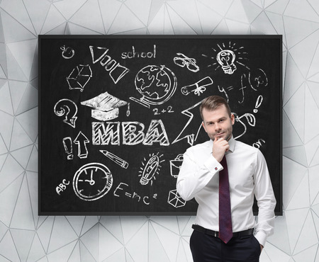 business degree: Senior manager is thinking about getting of the business degree. A concept of the MBA degree. Drawn educational icons on the chalkboard. Stock Photo