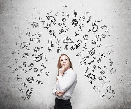 fondo de graduacion: Joven y bella mujer de negocios est� pensando en la optimizaci�n de procesos de negocio. Iconos de negocios dibuja sobre la pared de hormig�n.