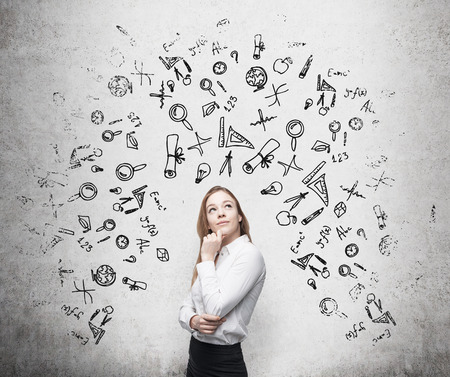 career job: Young beautiful business woman is thinking about optimisation business process. Drawn business icons over the concrete wall. Stock Photo