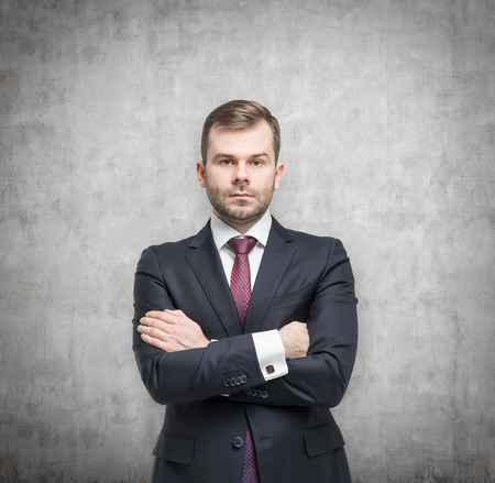 unyielding: Young handsome businessman in a suit is standing in a concrete room Stock Photo