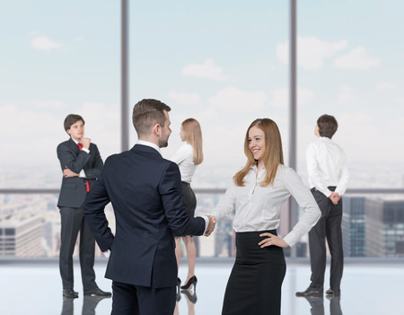 decision  making: Happy young professionals are standing in a contemporary glass office in New York. Handshake as a concept of successful decision making process. Stock Photo