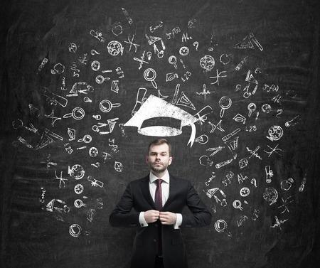 graduacion: Apuesto hombre de negocios joven está pensando acerca de la educación en la escuela de negocios. Dibujado iconos de negocios sobre el muro de hormigón oscuro. Sombrero de graduación.