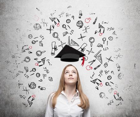 教育: 年輕漂亮的女商人在思考教育的商學院。拉業務圖標在水泥牆。畢業的帽子。