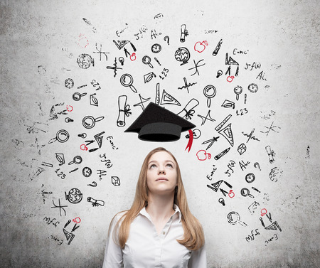 education choice: Young beautiful business woman is thinking about education at business school. Drawn business icons over the concrete wall. Graduation hat.