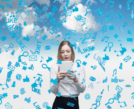 clouding: Beautiful young business woman is looking at the tablet. Social media icons are falling down over the sky background. Stock Photo