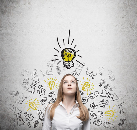 originality: Young beautiful lady is looking at the drawn yellow light bulb. The concept of the brainstorm of start up business.Concrete wall.