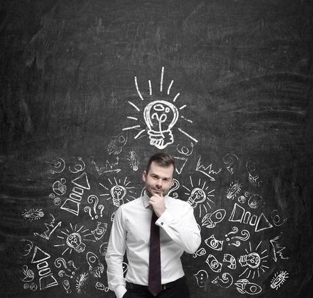 concepto: Encargado joven que est� pensando en nuevas ideas de negocio. Iconos de negocio y una bombilla de luz amarilla se dibujan en el muro de hormig�n oscuro.
