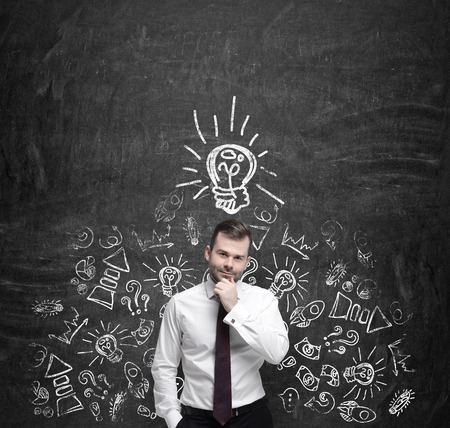 expertise concept: Young manager is thinking about new business ideas. Business icons and an yellow light bulb are drawn on the dark concrete wall. Stock Photo
