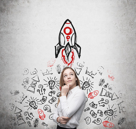 Young beautiful business lady is thinking about new business ideas. Business icons and a rocket are drawn on the concrete wall.