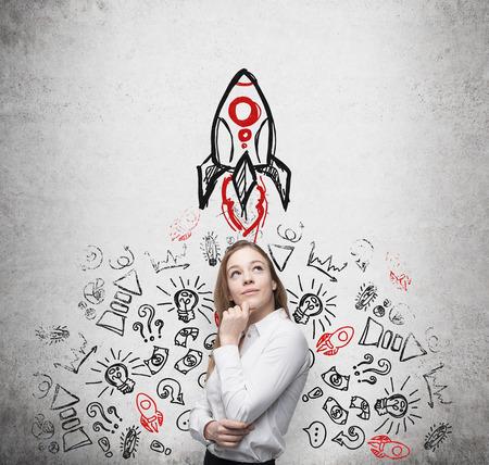cohetes: Se�ora hermosa joven empresa est� pensando en nuevas ideas de negocio. Iconos de negocio y un cohete se dibujan en la pared de hormig�n.