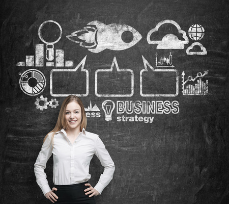 Beautiful analyst represents a successful business strategy flowchart. Chalk business icons are drawn over the black wall. photo