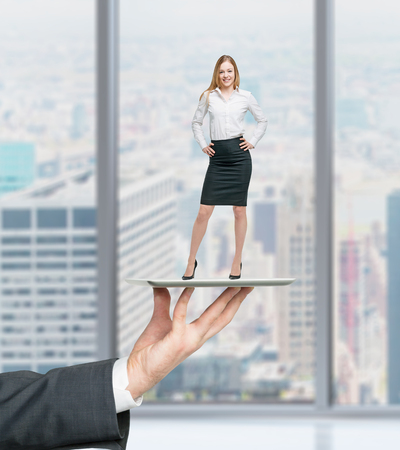 Businessman's hand is holding a gadget with standing beautiful employee on it. Human recourses concept. Banco de Imagens