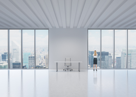 Rear view of the blonde employee who looks out the window in New York's panoramic office. A concept of the modern workplace.