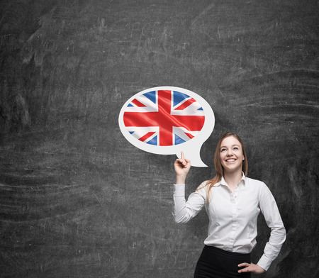 linguistics: Beautiful woman is pointing out the thought bubble with Great Britain flag. Dark background.