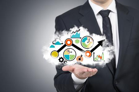 ビジネス: ビジネスマンは、開いた手のひらに業務フローチャートとクラウドを保持しています。灰色の背景。