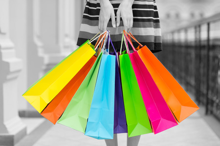 spendthrift: Woman holding colourful shopping bags at the mall. Black and white background.