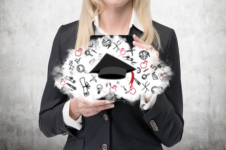 clouding: Blonde woman is holding a cloud with educational icons and a graduation hat. Concrete background.