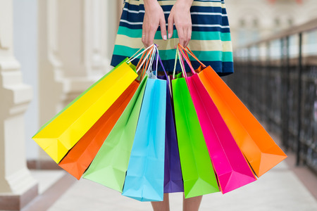body bag: Woman holding colourful shopping bags at the mall.