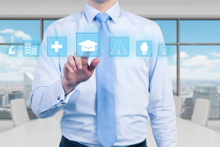 Een jonge manager in modern panoramisch kantoor is het indrukken van de educatieve icoon. Een concept van het bedrijfsleven het onderwijs. New York achtergrond. Stockfoto - 40765087