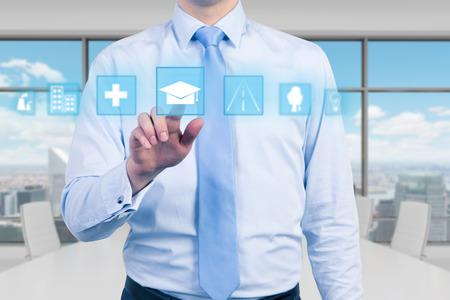 istruzione: Un giovane manager in ufficio moderno panoramico sta spingendo l'icona educativo. Un concetto di formazione aziendale. Sfondo di New York. Archivio Fotografico