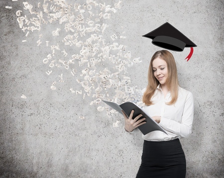A beautiful student is holding a black folder with flying out letters from the folder. Graduation hat above the lady's head. Concrete background.