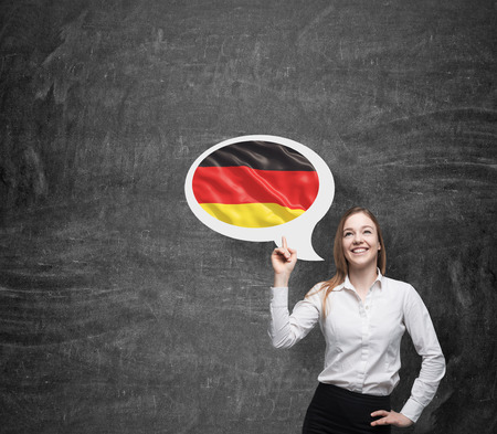 charisma: Beautiful woman is pointing out the thought bubble with German flag. Dark background.