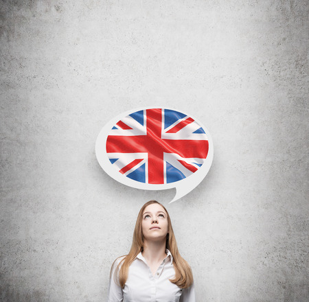 bandera reino unido: Mujer hermosa y la burbuja de pensamiento por encima de la cabeza con la bandera de Gran Breta�a. Fondo concreto. Foto de archivo