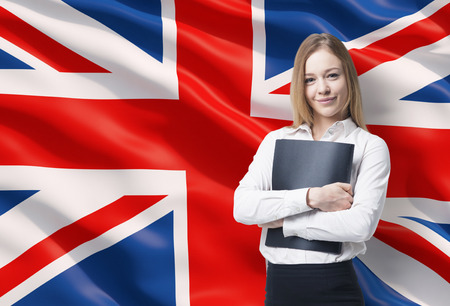 great britain flag: Smiling business lady in a white shirt with a black folder. Great Britain flag as a background.