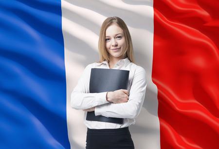 黒のフォルダーと白いシャツのビジネス女性の笑みを浮かべてください。背景としてフランスの国旗。