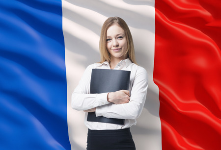 Smiling business lady in a white shirt with a black folder. French flag as a background.