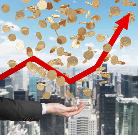 new economy: Close up of the open palm and falling golden dollar coins from the sky. Red arrow is going up as a symbol of the growth in economy. New York city background. Stock Photo