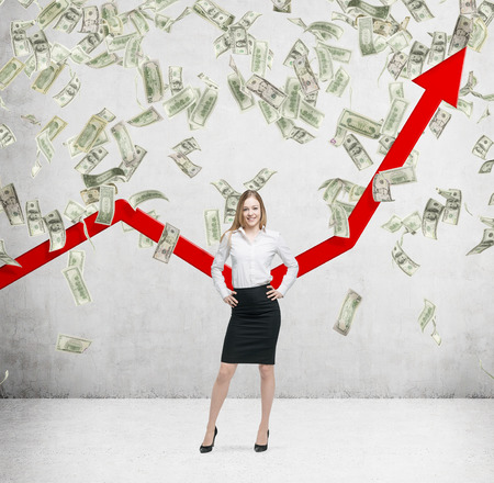red bills: Full-length smiling business lady stands among falling dollar bills from the ceiling. Red arrow is going up as a symbol of the growth in economy. Concrete background.