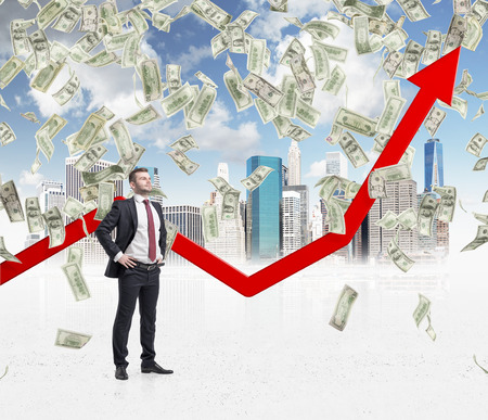 dollar symbol: Full-length confident businessman stands among falling dollar bills from the sky. Red arrow is going up as a symbol of the growth in economy. New York sketch background. Stock Photo