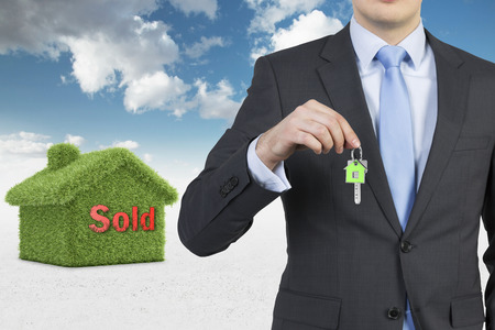 property agent: Confident real property agent is offering a key from a recently sold family house.
